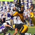 Iowa running back Damon Bullock jumps over Northern Iowa Panthers linebacker Jordan Gacke and Iowa Hawkeyes tight end C.J. Fiedorowicz.