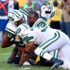 Jets linebacker Bart Scott loses his helmet as he collides with fellow linebacker Aaron Maybin and safety Yeremiah Bell to gang tackle wide receiver Jerricho Cotchery of the Steelers.