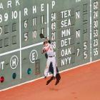 Orioles' outfielder Nate McLouth tries to scale Fenway Park's Green Monster in a game against the Boston Red Sox.