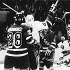 "As the 1984 postseason begins, the Isles seem ripe for the taking when the Rangers score first in each game of their first-round series against the four-time Cup champs and hold them without a power-play goal. Don Maloney sends the nerve-wracking, decisive Game 5 into overtime with a stunning (and disputed) tying tally with only 39 seconds to go in the third period. Then low-scoring defenseman Ken ""Wolfman"" Morrow (second from right) becomes an unlikely hero by driving a screen shot past Rangers goalie Glen Hanlon at 8:56 of OT to keep the Islanders' Drive for Five alive."