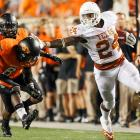 Texas running back Joe Bergeron (24) stiff arms Oklahoma State's Ashton Lampkin (6) during Texas's 41-36 win over the Cowboys.