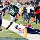 Jets running back Joe McKnight dives for a touchdown as the Texans' DeVier Posey (11) and Troy Nolan (33) look on.