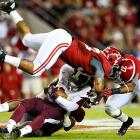 Crimson Tide defenders Nick Perry (33) and Trey DePriest collide while tackling Mississippi State tight end Malcolm Johnson in Tuscaloosa. Alabama remained undefeated after a 38-7 win.