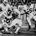 Ricky Bell becomes the first 1,000-yard rusher in team history when he gains 101 yards in a 23-22 loss to Minnesota. Bell finishes the season with 1,263 yard rushing yards.