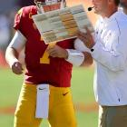 The quarterback and his head coach ponder the menu from Mr. Chow's during an easy win over Arizona State.
