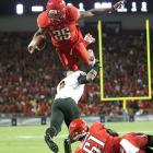 Wildcat strike: The NCAA's leading rusher took to the air over Arizona State safety Alden Darby and landed with a touchdown.