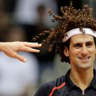 Djokovicing around at a hair-raising exhibition match in Rio de Janeiro against Gustavo 'Guga' Kuerten (left), who is giving him a hand.