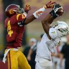 Oregon wide receiver Keanon Lowe goes up to snag a ball over USC's Torin Harris.