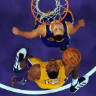 The Warriors' Stephen Curry and the Lakers' Dwight Howard gaze up at a ball near the rim during the Lakers 101-79 win.