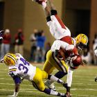 LSU's Kevin Minter and Micah Eugene team up to send Arkansas quarterback Brandon Mitchell flying.
