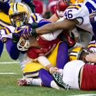 Arkansas quarterback Tyler Wilson is tackled just short of the goal line by LSU defenders. The Tigers improved to 10-2 with their 41-17 win over the Razorbacks.