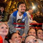Pacquiao poses for photos with fans during his arrival at the MGM Grand on Tuesday.