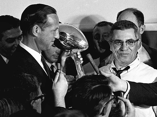 "When Lombardi (right) led the Packers to a Super Bowl I victory, commissioner Pete Rozelle presented him with a trophy that said ""World Professional Football Championship."""