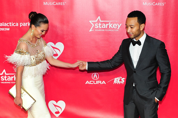 John gives Chrissy a hand while attending the MusiCares Person of the Year Benefit in Feb. 2013 :: REDERIC J. BROWN/AFP/Getty Images