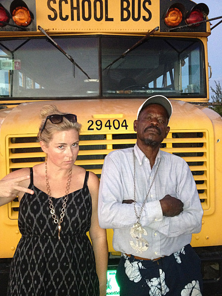 MJ Day poses with a  school bus and its driver while in the Bahamas, 2013 issue.