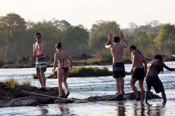 The crew swimming and trekking over the Zambezi River to Devils Pool in Zamiba, 2012 issue.