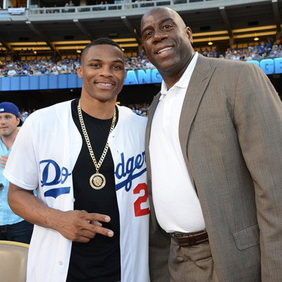 Russell Westbrook (left) attends a Dodgers game with Magic Johnson, opting for a traditional look. (Getty Images Entertainment)