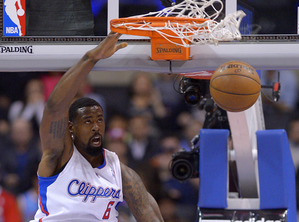 DeAndre Jordan makes a strange face while dunking during Wednesday's preseason game against the Jazz. (AP/Mark J. Terrill)