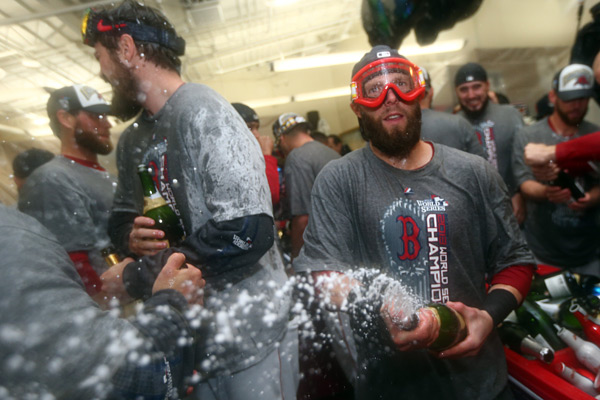 Dustin Pedroia celebrates in the Red Sox locker room following the victory. (Elsa/Getty Images)