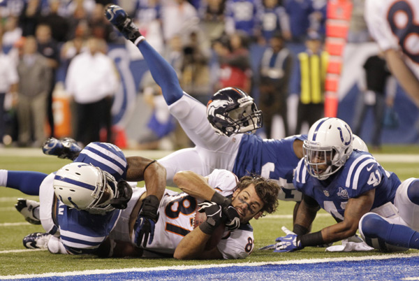 Eric Decker loses his helmet while making a reception during Sunday's Broncos-Colts game. (AJ Mast/AP)