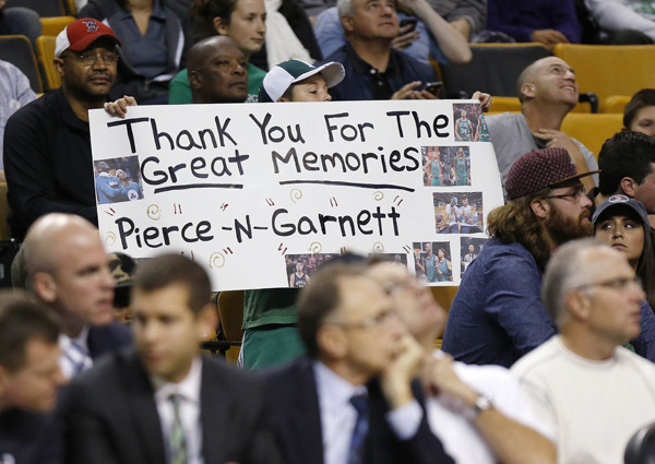 Celtics fans pay respect to Paul Pierce and Kevin Garnett during Wednesday's preseason game against the Nets. Neither player made the trip. (AP/Michael Dwyer)
