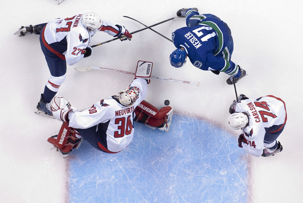 Ryan Kessler tries to knock the puck past Michal Neuvirth during Monday's Canucks-Capitals game. (Rich Lam/Getty Images)