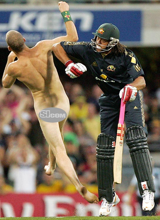 Australia's Andrew Symonds knocks over a streaker who ran onto the field during the Commonwealth Bank Series One Day International match between Australia and India in Brisbane, Australia.