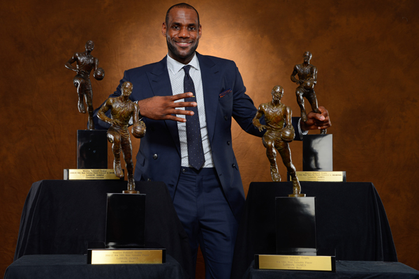 LeBron James in a blue suit posing with his four MVP awards. (Jesse D. Garrabrant/Getty Images)
