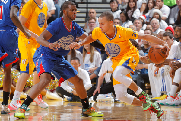 Clippers guard Chris Paul (left) and Warriors guard Stephen Curry (right) in their Christmas Day jerseys. (Rocky Widner/Getty Images)