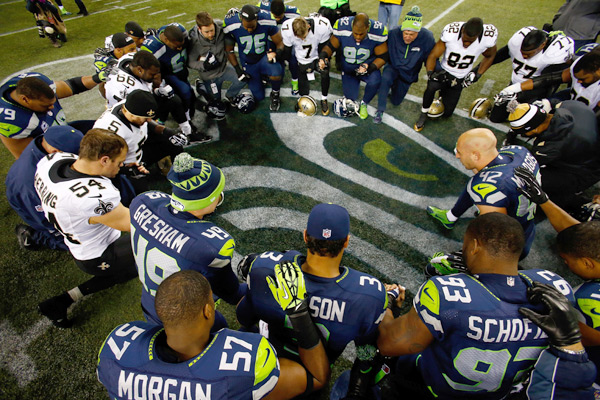 Postgame prayer circle :: Jonathan Ferrey/Getty Images