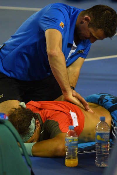 Nadal receiving some massage therapy for his ailing back. (AFP/Getty Images)