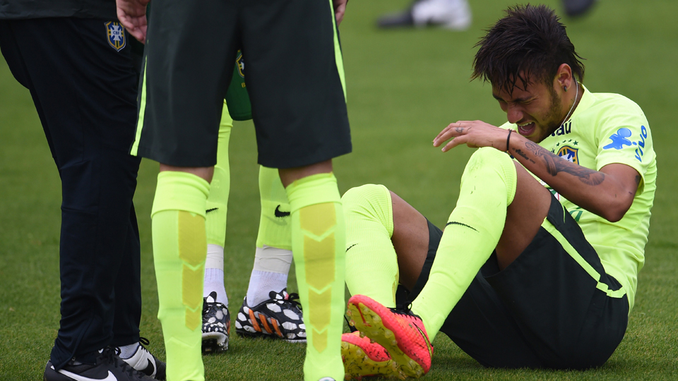 Neymar grimaces after rolling his ankle in Brazil's training session on Monday, but he was able to carry on, according to Brazilian reports.
