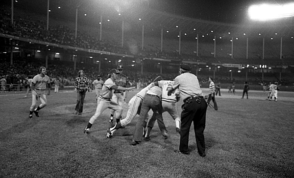 The  Rangers take down an unruly fan who ran onto the field.  (Getty Images)