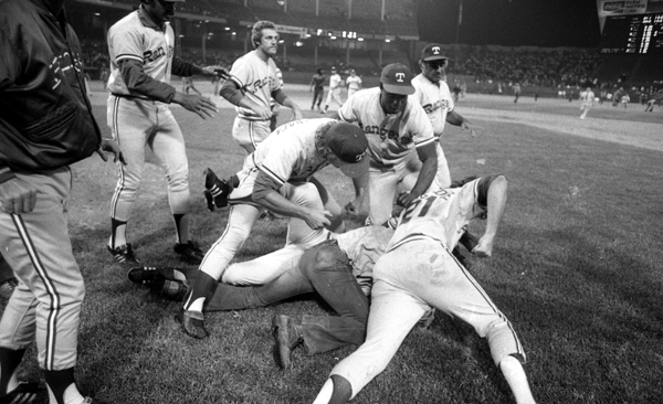 Members of the  Rangers take down a fan who ran onto the field.  (Getty Images)