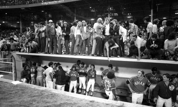 Indians fans stand on top of the Cleveland dugout. (Getty Images)