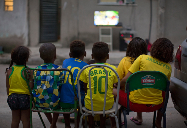 Brazilian children watch the World Cup's opening game in an alley in the Mangueira slum in Rio de Janeiro.