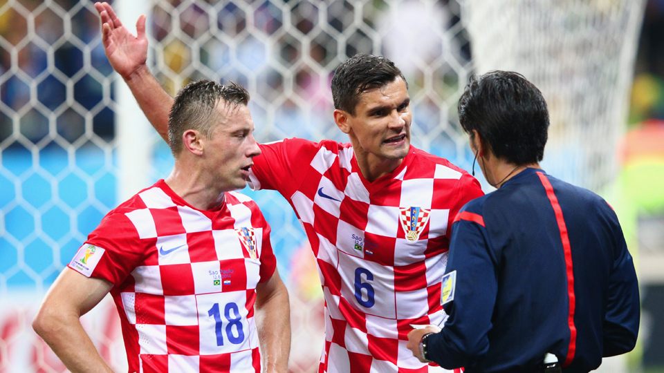 Croatia's Dejan Lovren, center, pleads his case to referee Yuichi Nishimura, whose penalty call provided Brazil with a chance to take the lead in the teams' World Cup opener.