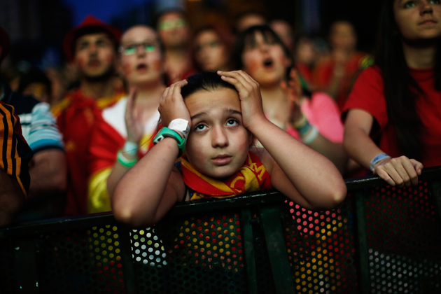 A young Spain fan in Madrid watches in dismay as her beloved Furia Roja are eliminated from the World Cup in stunning fashion.