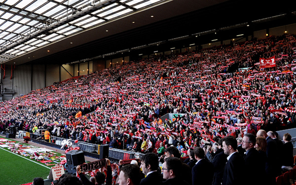 Fans in the Kop End at Anfield raise their scarves during Tuesday's memorial service. (Liverpool FC)