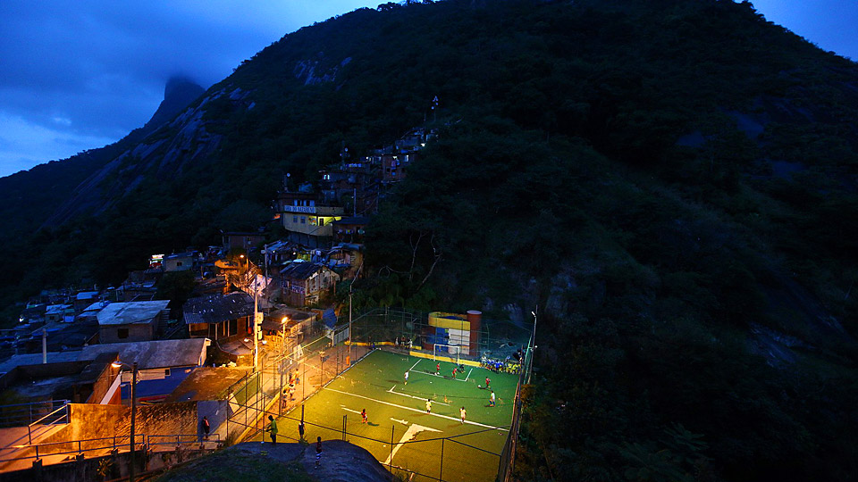 Children play soccer on a field thousands of feet above the Rio from the postcards, a grass area lined with a fence.