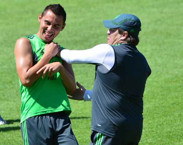 Miguel Herrera, right, jokes with Mexican defender Paul Aguilar during training ahead of Sunday's round of 16 match vs. the Netherlands