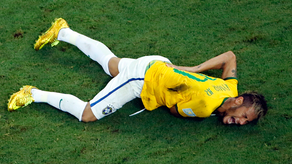 Brazil star Neymar holds the place on his back where Camilo Zuniga's knee fractured a vertebra, ending his World Cup in the process.
