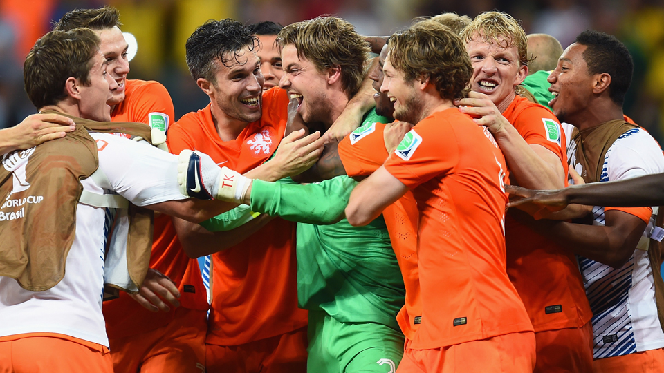 Netherlands backup goalkeeper Tim Krul, center, is mobbed by teammates after his heroics in the penalty shootout to lift the Dutch over Costa Rica in the World Cup quarterfinals.