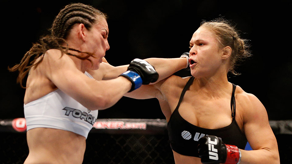Women's bantamweight champion Ronda Rousey (right) punches Alexis Davis in their championship fight at UFC 175.