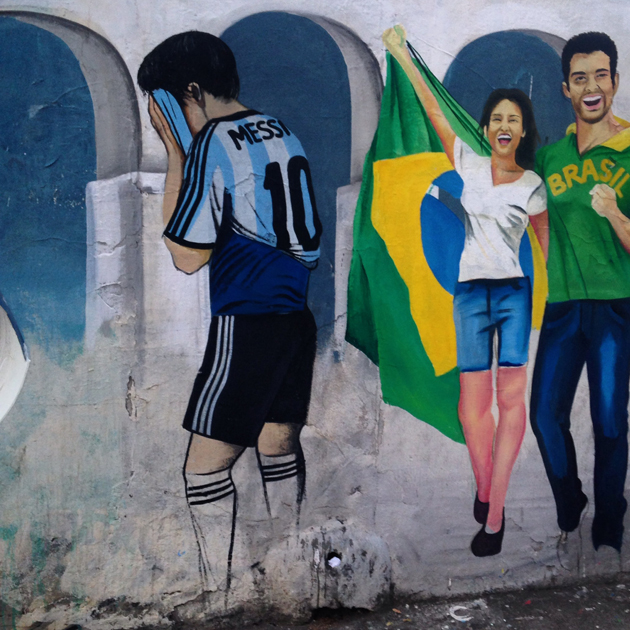 Roadside graffiti in Rio de Janeiro depicts a disappointed Lionel Messi, one with his head in his hands.