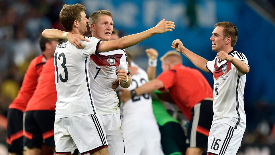 Bayern Munich and Germany teammates (L-R) Thomas Muller, Bastian Schweinsteiger and Philipp Lahm share a celebratory hug after capturing the World Cup title on Sunday.