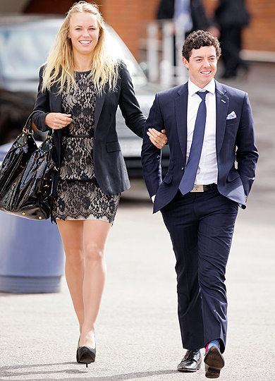 Caroline Wozniacki and golfer Rory McIlroy walk arm-in-arm.