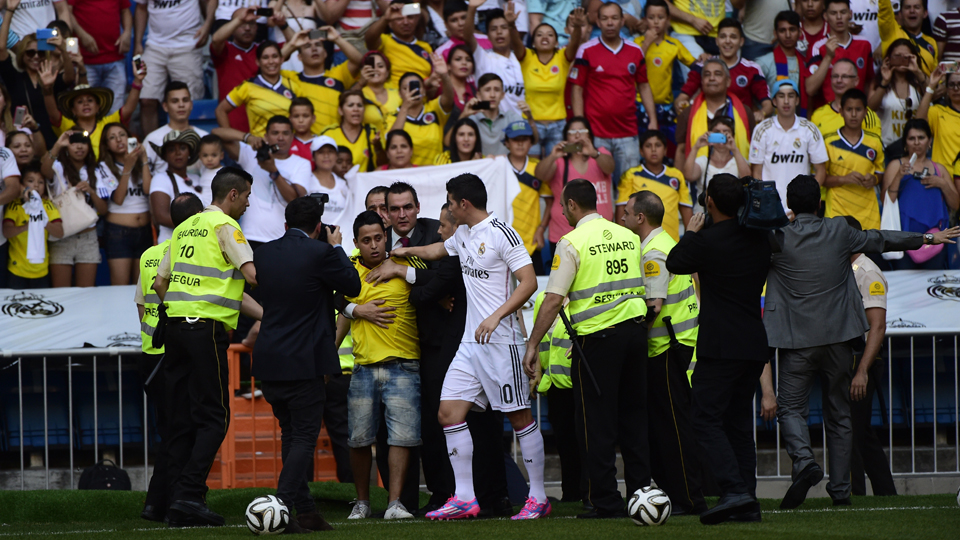 James Rodriguez confronts a pitch invader during his presentation at Real Madrid's Estadio Santiago Bernabeu on Tuesday.