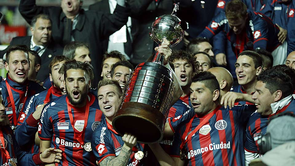 Julio Buffarini (center) of Argentina's San Lorenzo holds the trophy after defeating Paraguay's Nacional in the 2014 Copa Libertadores championship.