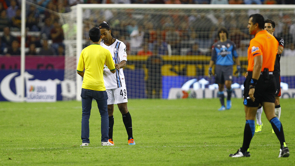 Ronaldinho signs an autograph on the shirt of a pitch invader during Queretaro's 2-1 loss to Atlas Tuesday night.